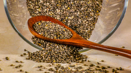 Glass container and wooden spoon with chia seeds