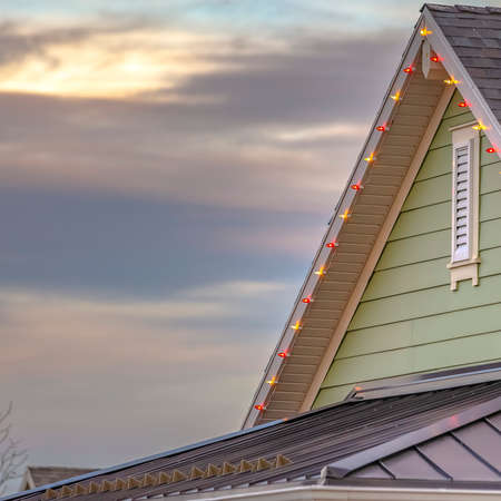 Christmas lights on the edge of the roof of a home in Daybreak Utah. The lights are various colors and the house is green and can be seen with the sky behind at sunset. Stock Photo