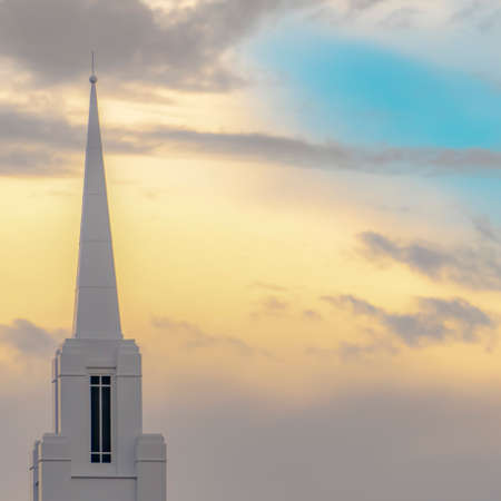 Church steeple with copy space behind in the sky. The sky shows pinks, purples, blues and golden light from the sunset. Located in Eagle Mountain Utah.