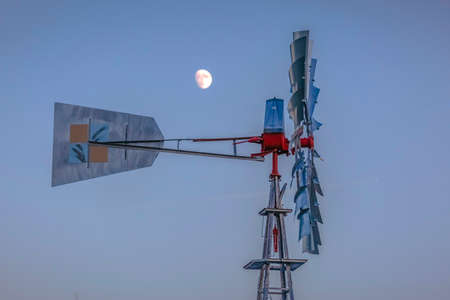 Close view of windmill and moon in sky behind the windmill in Utah Valley just after sunset or blue hour. The sky looks purple and the windmill is metal aluminum located in Saratoga Springs, Utah. Banco de Imagens