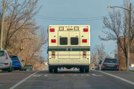 Ambulance on a road near a school against sky
