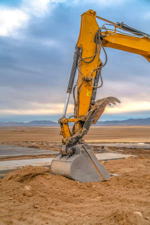 Excavator arm and bucket against mountain and sky