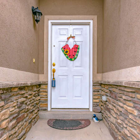Narrow entryway of a home with white front door