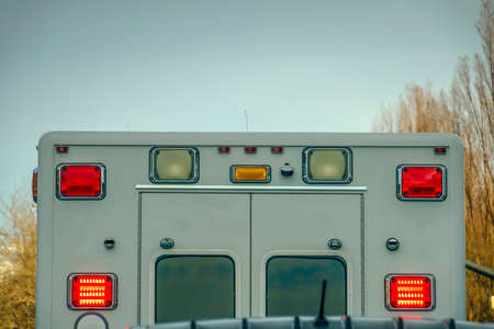 Rear view of an ambulance against trees and sky Stock Photo
