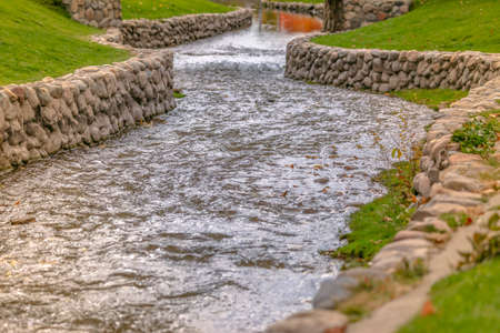 Sparkling stream curving through a trimmed lawn