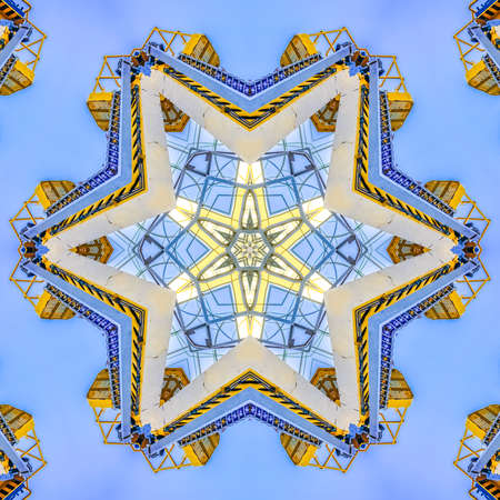 Cherry picker on construction site in the day. Geometric kaleidoscope pattern on mirrored axis of symmetry reflection. Colorful shapes as a wallpaper for advertising background or backdrop.