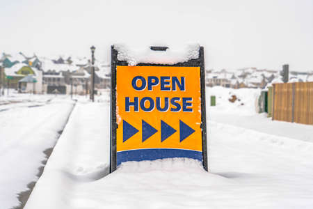 Open House sign against snow covered landscape. An Open House sign pointing to a property that is for sale in Daybreak, Utah. The bright sign stood in stark contrast against the snowy landscape. Фото со стока