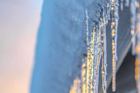 Roof with icicles reflecting sunlight in Utah. Close up view of a frosted roof with shiny icicles reflecting the golden sunlight. Winter scenery in Eagle Mountain, Utah on an icy day in December.
