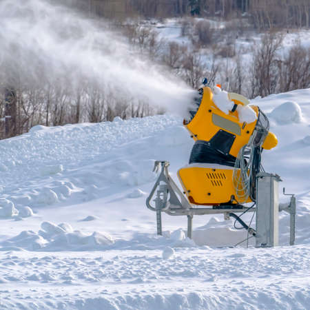 Snow cannon at work on a sunny winter day in Utah. Bright yellow snow cannon working on a sunny winter day in Park City, Utah. Powdery artificial snow showers out from the nozzle of the machine.