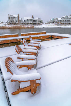 Snowy chairs on lake deck with view of homes