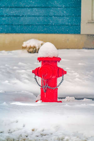 Vibrant red fire hydrant against powdery snow. Red fire hydrant on snow covered ground in Daybreak, Utah. The vibrant fire pump stood in stark contrast against the powdery white snow background.