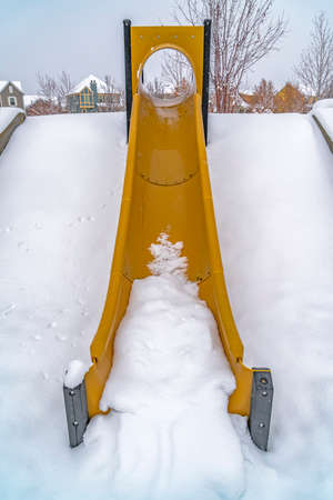 Vibrant slide against powdery snow in winter. Vibrant yellow slide against powdery white snow covering a slope in winter. Daybreak, Utah homes with snowy roofs can be seen in the background.