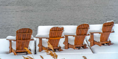 Lake deck with chairs on snowy winter day in Utah. Lake deck with wooden chairs facing the water in Daybreak, Utah. The chairs and deck are covered with a sheet of powdery white snow in winter.