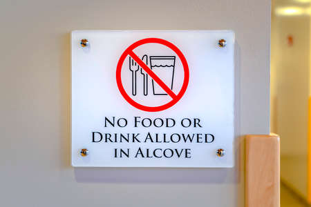 No Food or Drink Allowed In Alcove sign. Close up of a No Food Or Drink Allowed sign on the white wall of a building. The sign informs people that food and drinks are not allowed inside the alcove.
