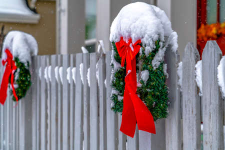 Christmas wreaths on picket fence in Daybreak Utah. Christmas wreaths on white picket fence of a home in Daybreak, Utah. The red ribbons add a cheerful look to the snow covered surroundings. Stock Photo