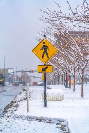 Pedestrian Crossing sign on a snowy sidewalk