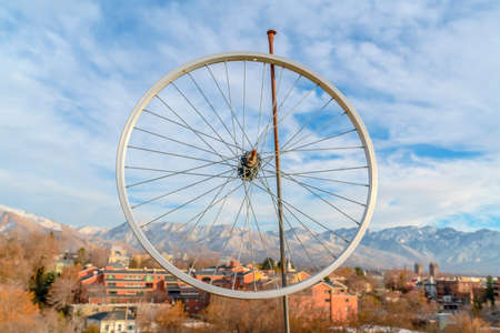 Bicycle wheel rim against homes mountain and sky