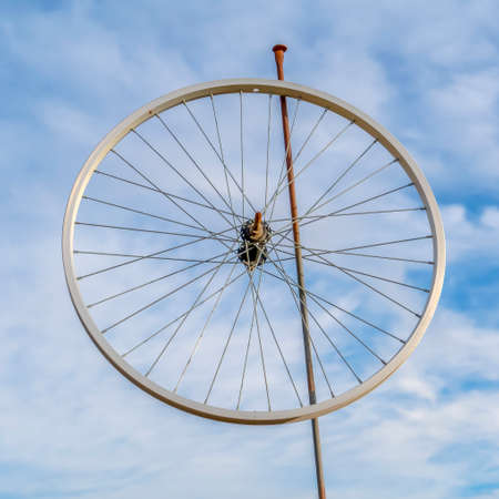 Bicycle wheel rim on a pole against cloudy sky