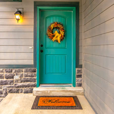 Blue green front door with a welcoming wreath
