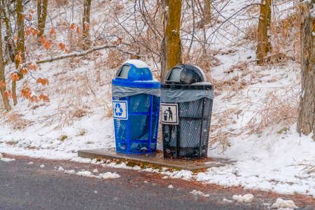 Garbage cans beside a road and snowy slope
