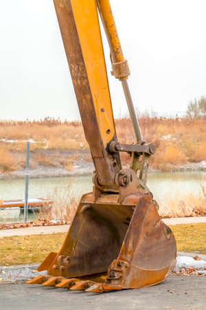 The dirty dipper and bucket of a yellow excavator