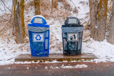 Trash cans with snowy slope and trees background 写真素材