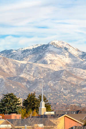 Rooftops against Wasatch Mountain and cloudy sky