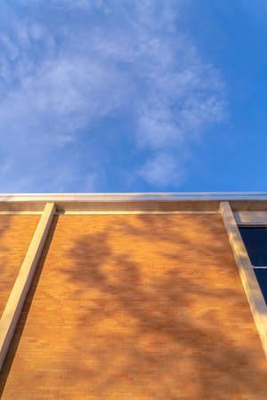 Wall of a building with shadows against blue sky