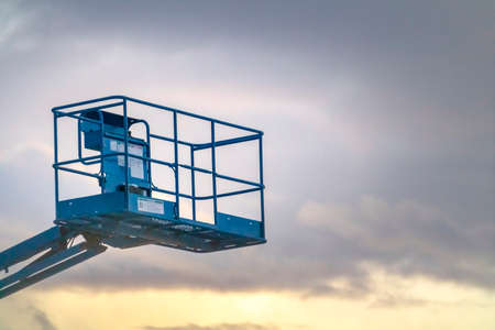 Boom lift against cloudy sky in Eagle Mountain. Close up of an empty blue boom lift against cloudy sky in Eagle Mountain, Utah. An aerial work platform used to reach inaccessible high areas.