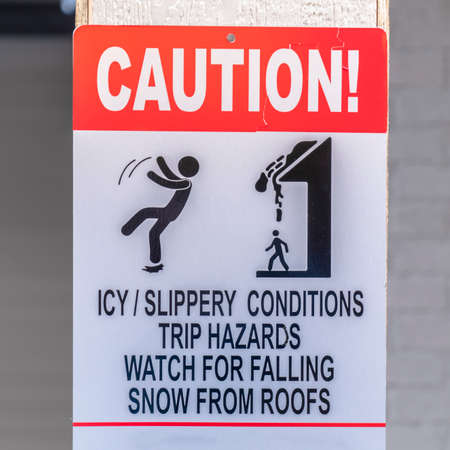 Caution sign on a snowy area in winter. Caution sign on a snowy area in winter. The sign alerts people to trip hazards on icy or slippery areas and to watch out for falling snow from roofs. Stok Fotoğraf - 119367277