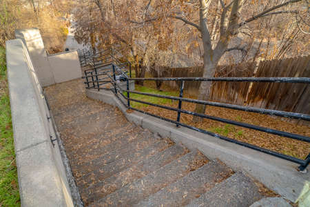 Staircase leading to a road in Salt Lake City. Looking down at an outdoor staircase leading to a road on a sunny day in Salt Lake City. An old brown wooden fence can be seen along the stairway.