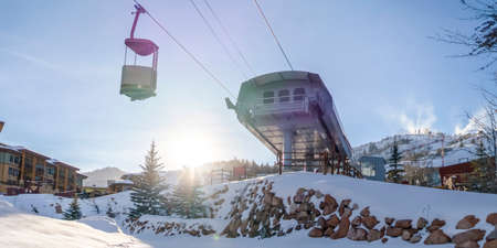 Sunlight beaming down on a ski resort in Park City. Bright sunlight behind a snowy mountain beaming down on the snow covered mountain at a ski resort with view os a ski lift against vast sky. 免版税图像