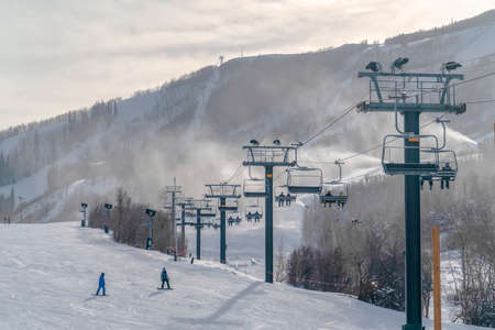 Scenic ski resort with ski lifts in Park City Utah. A scenic ski resort with ski lifts over the snow covered mountain in Park City. Skiers can be seen on the piste and chair lifts beneath the cloudy sky. Imagens - 119441984