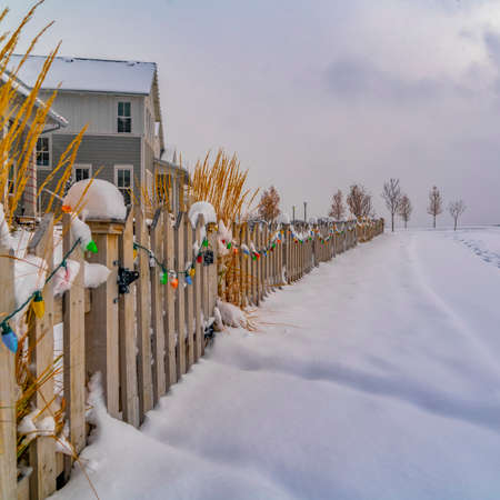 Colorful lights on wooden fence in Daybreak Utah. Colorful lights lining the wooden fence of a home in Daybreak, Utah. Footprints can be seen on the snowy road with view of cloudy sky in the distance.