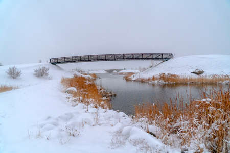 Oquirrh Lake with snowy shore and bridges in Utah. View of Oquirrh Lake on a frosty day in December in Daybreak with bridges against vast sky. Powdery white snow covers the lake's shore in winter.