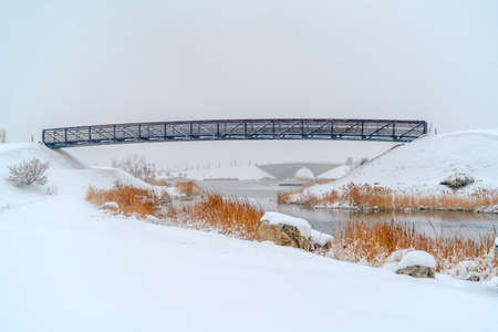 Bridges over Oquirrh Lake surrounded with snow. Bridges over the shiny water of Oquirrh Lake in Daybreak, Utah against sky. The calm lake is surrounded by powdery white snow in winter.