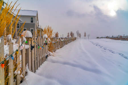 Winter landscape against cloudy sky in Daybreak. A scenic winter landscape against cloud filled sky in Daybreak, Utah. Footprints on snowy road can be seen in front of a wooden fence with lights.