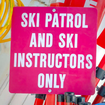 Ski Patrol and Ski Instructors Only sign close up. Only against ski equipment at a ski resort in Park City, Utah on a sunny day.