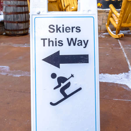 Skiers This Way sign at a ski resort. Close up of a foldable directional sign against a snowy floor and wooden rocking chairs. It points to the direction where skiers at the ski resort should go.