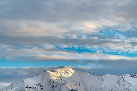 Remarkable sunlit mountain covered with powdery white snow in winter