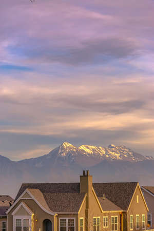 Facade of a home viewed against a snow capped mountain in the background