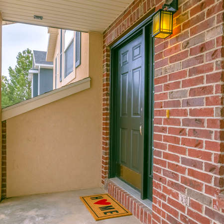 Clear Square Facade of a home with a small porch and classic red brick wall Stock Photo - 122761025