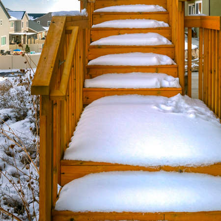 Clear Square Outdoor wooden staircase of a home covered with snow during winter season