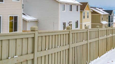 Klares Panorama Äußeres von Häusern in einem Holzzaun gegen eine verschneite Landschaft im Winter