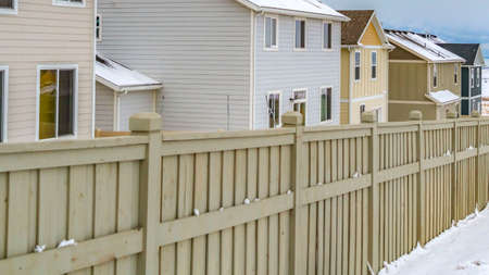 Panorama claro del exterior de las casas dentro de una valla de madera contra un paisaje nevado en invierno