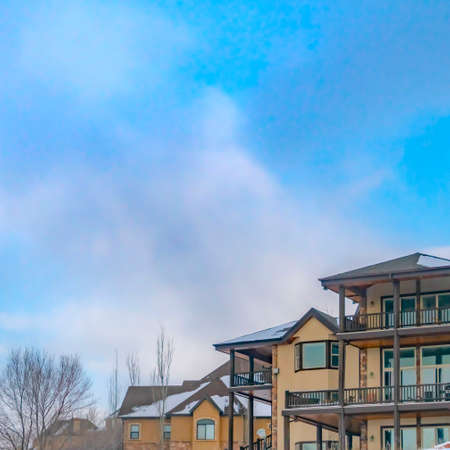 Square Appealing mountain home with a cloudy blue sky background in winter Imagens