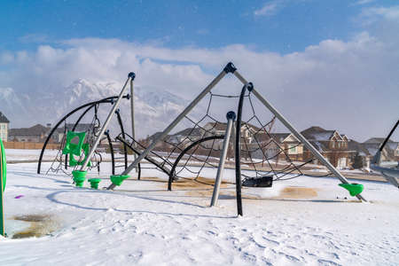 Climbing frames on a playground blanketed with snow on a sunny winter day