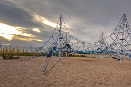 Rope climbing frame at a playground against a cloud filled sky at sunset