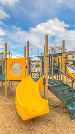 Clear Vertical Playground with a bright yellow slide under the vivid sky with puffy clouds