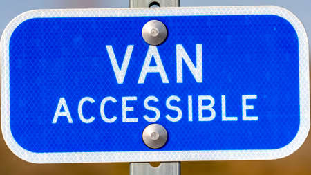 Clear Panorama Blue sign with a Van Accessible text on a parking area for handicapped people